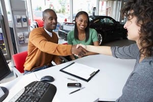 Young couple and car sales rep shake hands